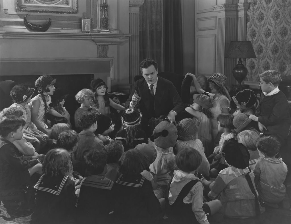 a monochrome picture of a man telling a story to a crouwd