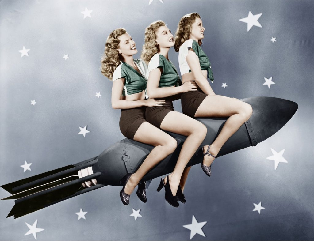 three girls are flying on a rocket